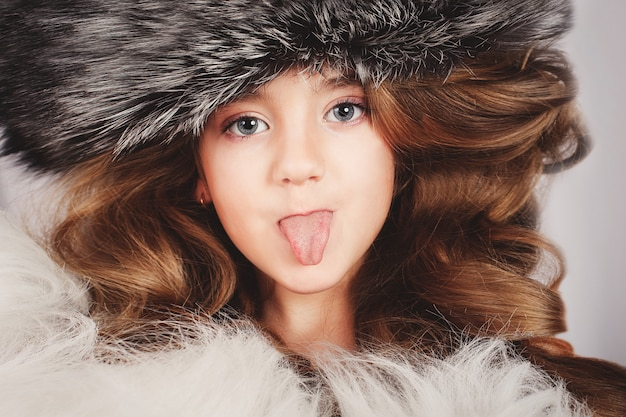 Portrait Of A Beautiful Young Girl In Fur Cap Puts Out The