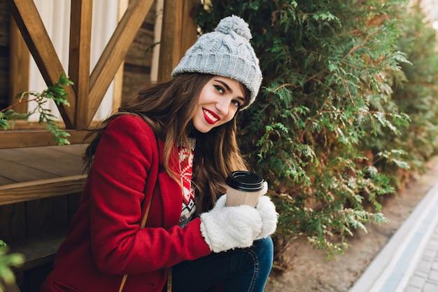 Bella ragazza del ritratto con capelli lunghi in cappotto rosso che si siede sulle scale di legno all'aperto. ha un cappello lavorato a maglia grigio, guanti bianchi, tiene il caffè e sorride. Foto Gratuite