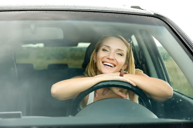 Portrait of beautiful young happy woman in the new car  - outdoors Free Photo