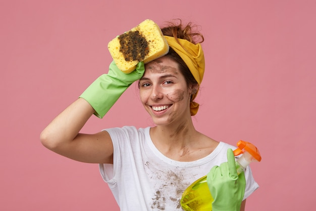 Portrait of beautiful young housewife with dirty clothes and face holding mop and washing spray holding hand on head looking tired but happy to finish work. tired cute woman doing house cleaning Free Photo