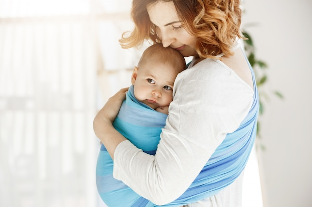 Portrait of beautiful young mother holding tight her newborn baby boy with love and caring. she smiling and feeling happiness of maternity moments. Free Photo