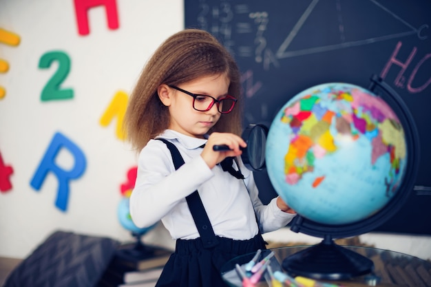 Portrait of a beautiful young schoolgirl girl exploring the globe through a magnifier. Premium Photo