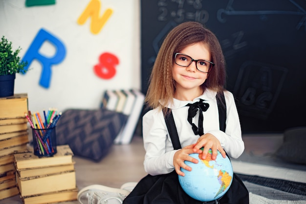 Portrait of a beautiful young schoolgirl girl holding globe sitting on the floor on the rug. Premium Photo