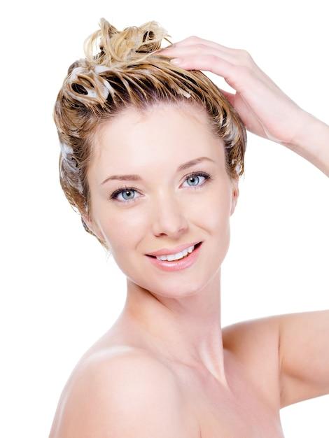 Ritratto di bella giovane donna sorridente che lava i suoi capelli isolati su bianco Foto Gratuite