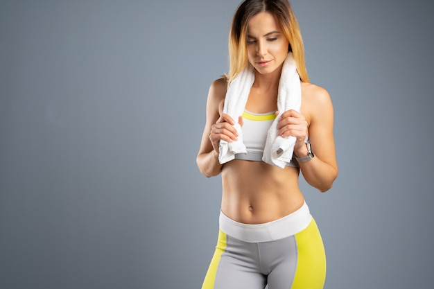 Portrait of a beautiful young sporty  woman against gray Premium Photo
