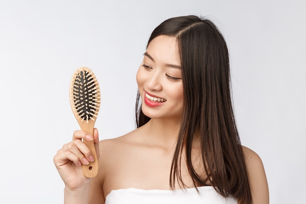 Portrait of a beautiful young woman comb wonderful hair isolated ...