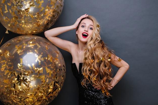 長い巻き毛のブロンドの髪、赤い唇、金色のティンセルでいっぱいの大きな風船を持つ、黒い豪華なドレスを着た美しい若い女性の肖像画。お祝い、驚き、前向き。 無料写真