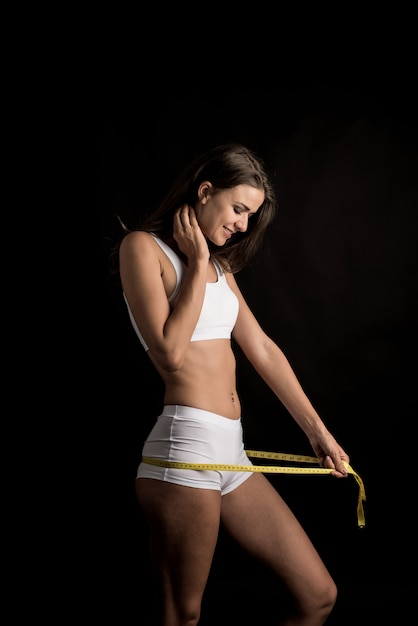 Portrait of beautiful young woman measuring her figure size with tape measure Free Photo