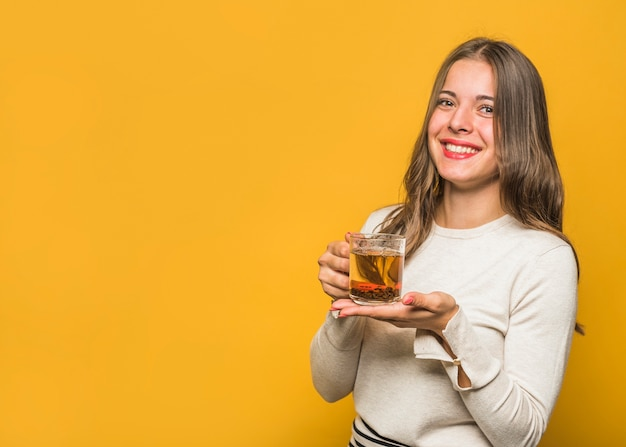 Portrait of a beautiful young woman showing herbal tea glass cup against yellow background Free Photo