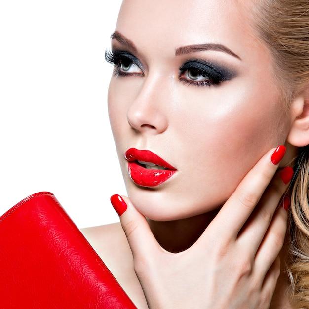 Ritratto di bella giovane donna con labbra e unghie rosso brillante. concetto - trucco moda glamour Foto Gratuite