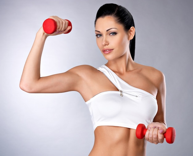 Portrait of beautiful young woman with dumbbells -  grey studio space. healthy lifestyle concept. Free Photo