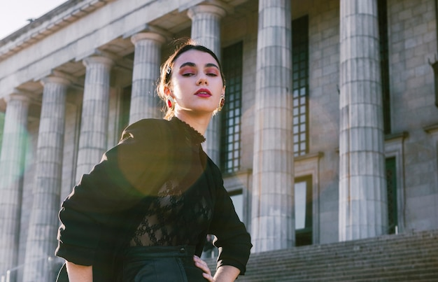 Portrait of a beautiful young woman with hands on hip in front of colonnade Free Photo