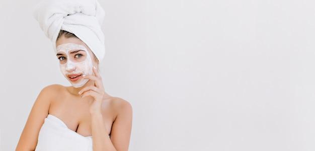 Ritratto di bella giovane donna con asciugamani dopo fare il bagno fa maschera cosmetica sul viso. Foto Gratuite