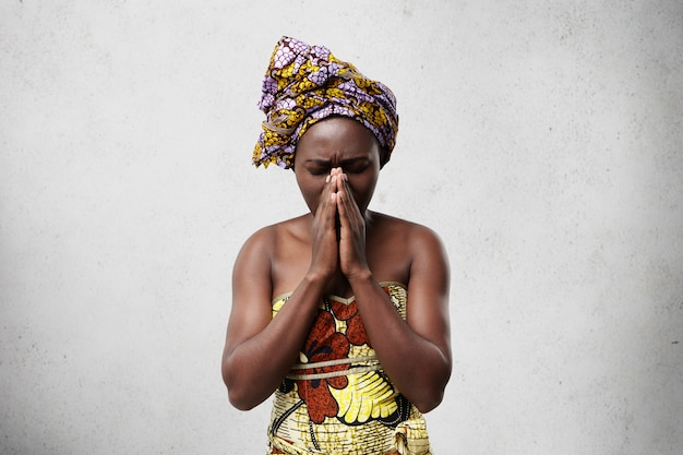 Portrait of begging black woman in traditional clothes pressing her palms together closing her eyes imploring for good luck of her children. religious african housewife praying for wellness of family Free Photo
