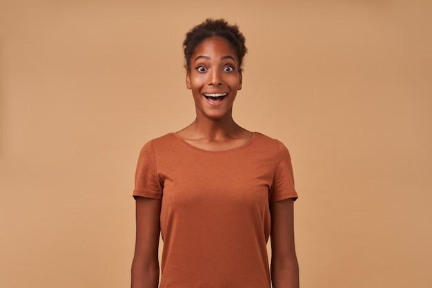 Ritratto di perplessa giovane femmina bruna riccia mantenendo la bocca spalancata mentre guarda sorpreso, isolato su beige in abbigliamento casual Foto Gratuite