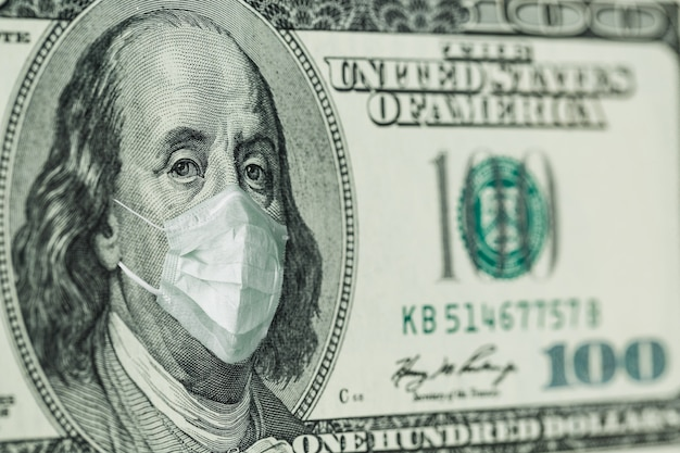Premium Photo | Portrait of benjamin franklin 100 dollar bills with a  medical mask from the coronavirus covid-19.