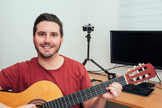 Portrait of a blogger playing guitar from his home recording studio. Premium Photo