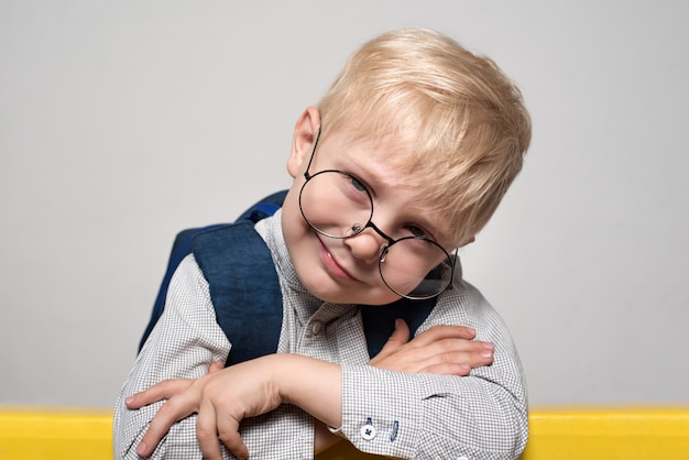 Portrait of a blond smiling boy in glasses and with a school backpack. school concept Premium Photo