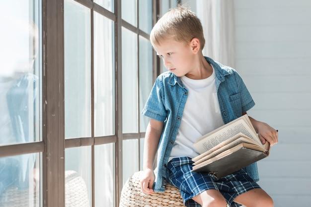 Portrait of a blonde boy sitting near the window in sunlight Free Photo