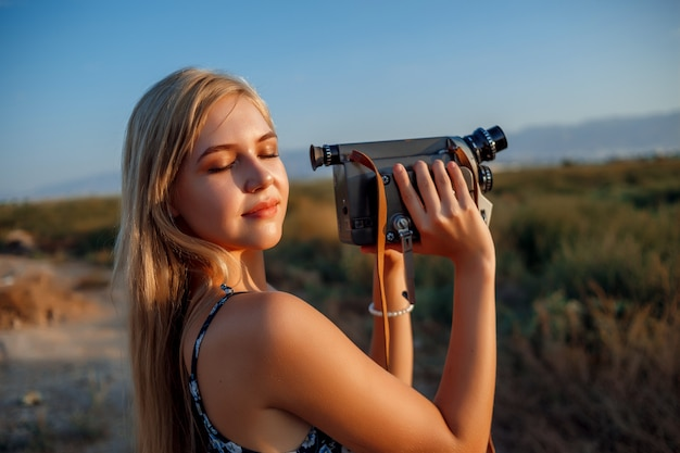 Portrait of blonde woman in floral print dress with vintage video camera in grape field during sunset Premium Photo