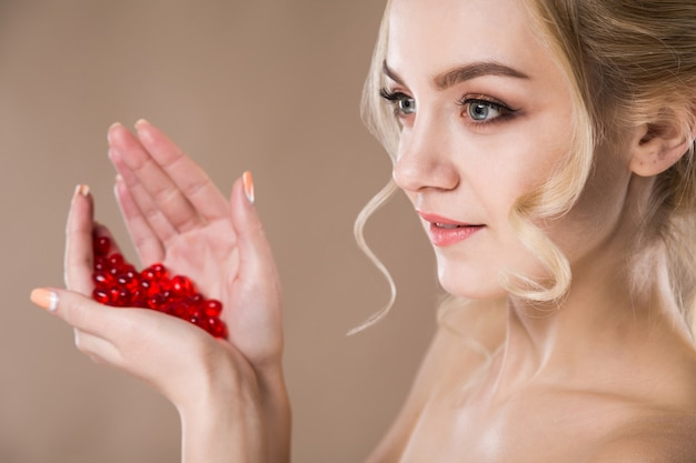 Portrait of a blonde woman with red capsules of vitamins in her hands Premium Photo