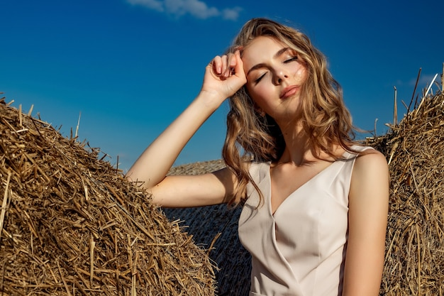 Portrait of a blonde young girl model who stands and poses on a sunny day Premium Photo