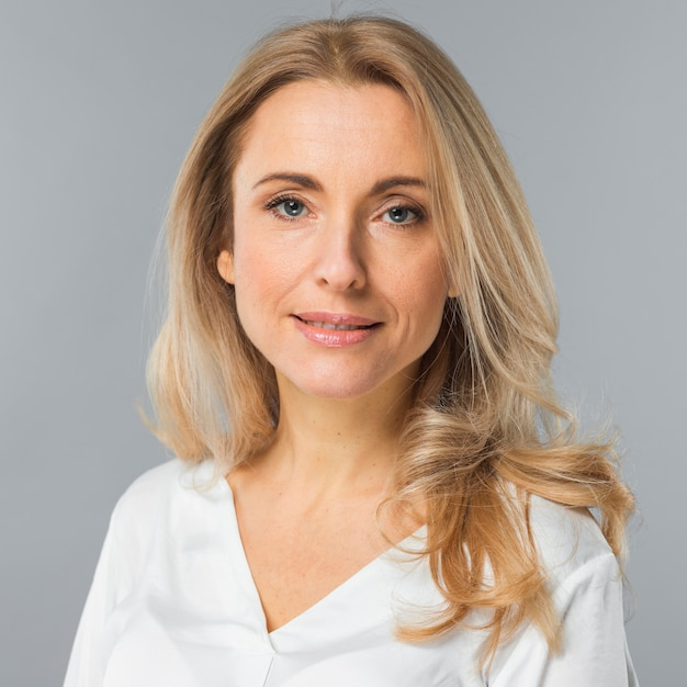 Portrait of blonde young woman looking at camera against gray background Free Photo