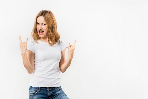 Portrait of a blonde young woman showing rock and roll gesture against white backdrop Free Photo
