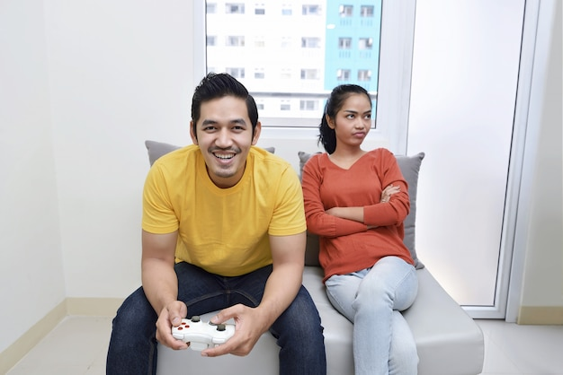 Portrait of bored asian woman while her boyfriend playing video games Premium Photo