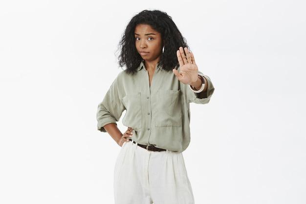 Ritratto di donna dalla carnagione scura adulta fiduciosa e dispiaciuta prepotente con taglio di capelli ricci che tiene la mano sulla vita che tira il palmo Foto Gratuite