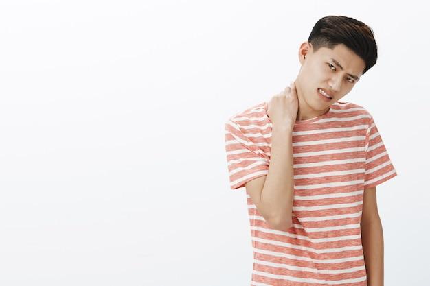 Ritratto di giovane uomo asiatico inquieto infastidito in maglietta a strisce riluttante a fare qualcosa che si strofina il collo inclinando la testa e accigliato esprimendo dispiacere Foto Gratuite