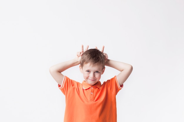 Portrait of boy child showing finger behind his head and teasing against white background Free Photo