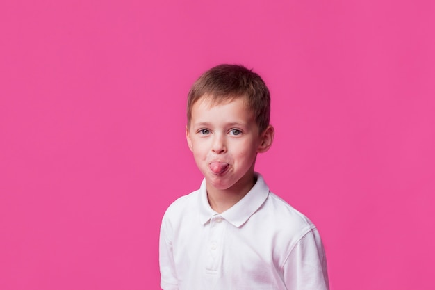 Portrait of boy child sticking out his tongue on pink backdrop Free Photo