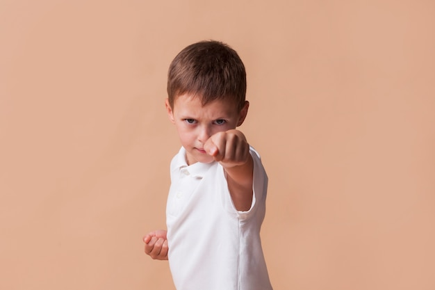 Portrait of boy clinching his fist for fighting on beige backdrop Free Photo