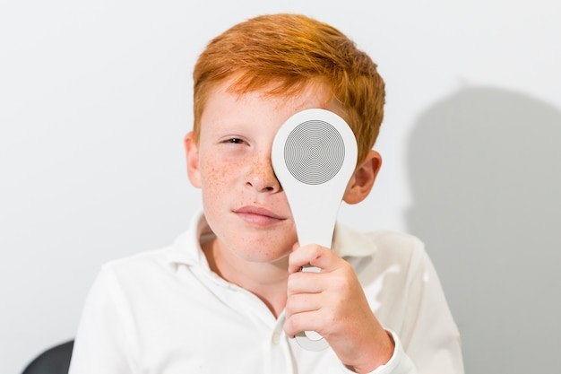 Portrait of boy covered eye with occluder in optics clinic Free Photo