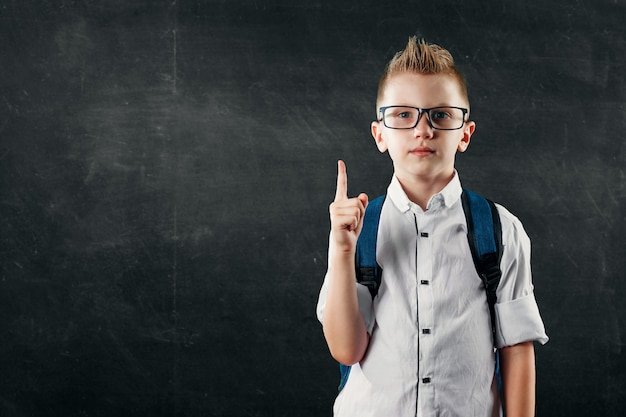 Portrait of a boy from an elementary school on a background of a school board Premium Photo