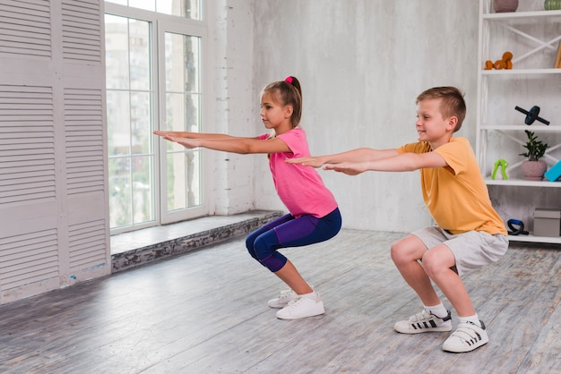Portrait of a boy and girl exercising at home Free Photo