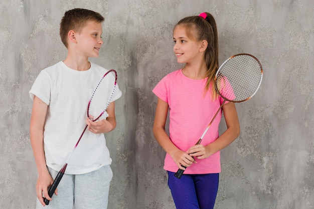 Portrait of a boy and girl holding racket in hand standing in front of concrete wall Free Photo