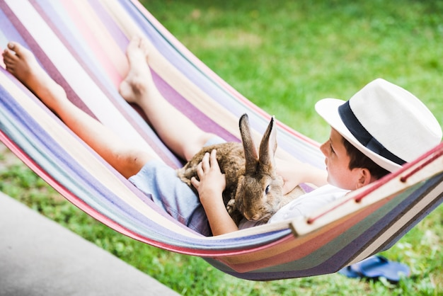 Portrait of boy lying on hammock with rabbit in hand Free Photo