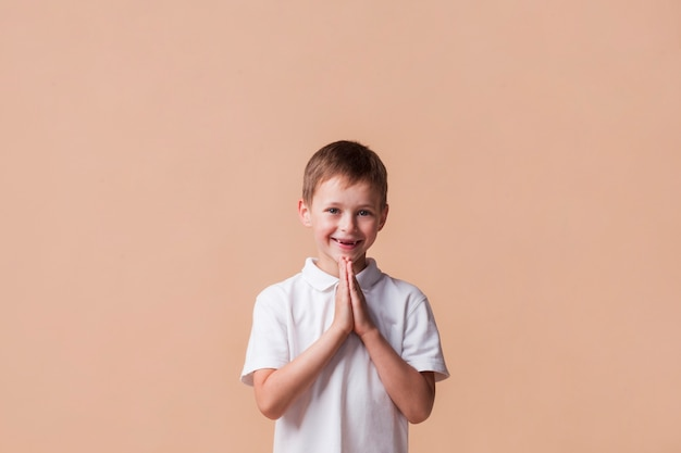 Portrait of boy praying with a smile on his face over beige backdrop Free Photo