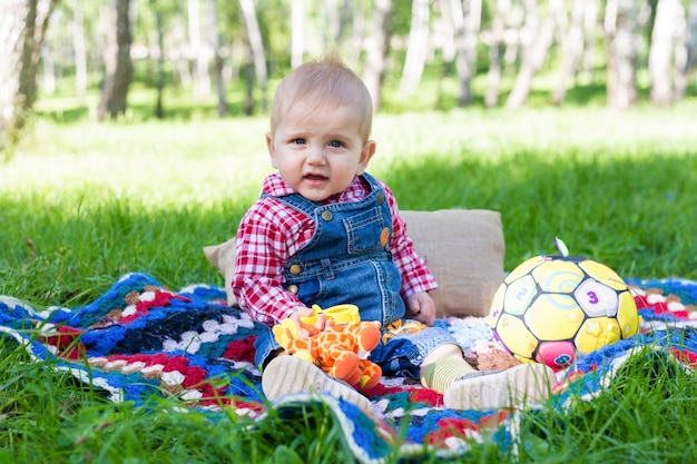 Portrait of a boy sitting on a blanket on a fresh grass in a city park in summer Premium Photo