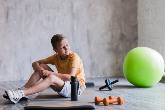 Portrait of a boy sitting near the pilates ball; dumbbell; roller slide and water bottle in gym Free Photo
