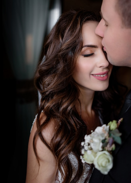 Portrait of bride and groom madly in love with closed eyes, wedding day, wedding photo Free Photo