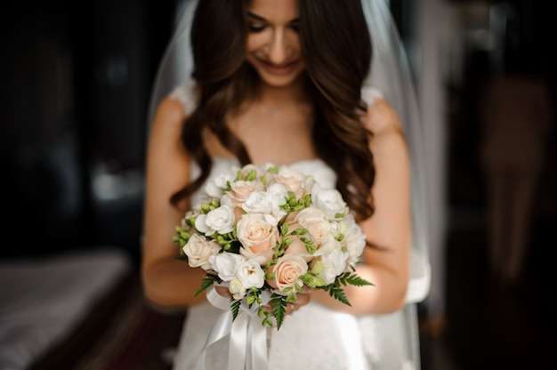 Portrait of bride in long dress and stylish bouquet with roses Premium Photo