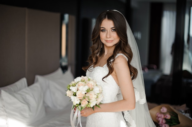 Portrait of bride in wedding dress,veil and bouquet with roses and fern Premium Photo