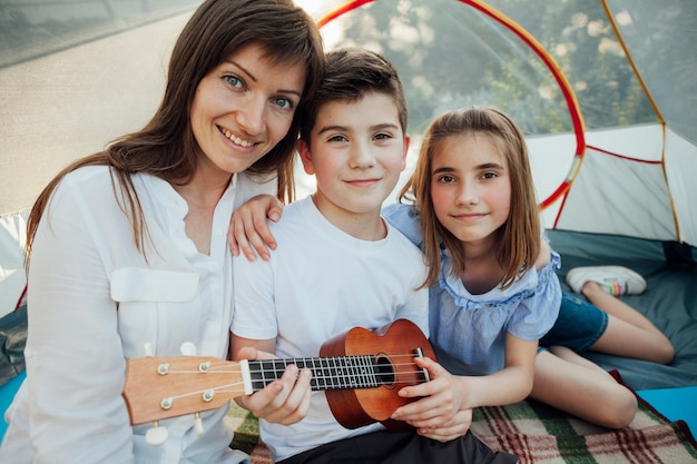 Portrait of brother and sister holding ukulele sitting with their mother in tent Free Photo