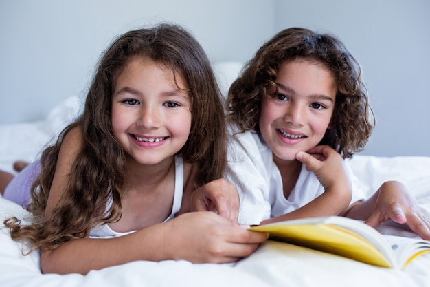 Portrait of brother and sister reading book together on bed Premium Photo