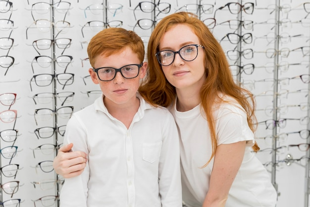 Portrait of brother and sister with spectacle in optics store Free Photo