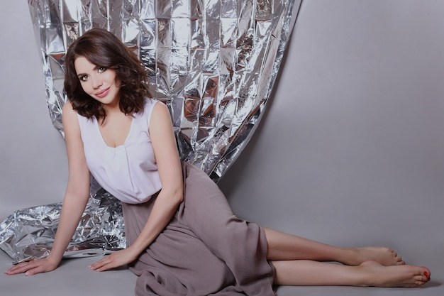 Portrait of a brown haired woman with a beautiful professional makeup on a shiny background. sexy girl with nice clean skin and bright lipstick on her lips Premium Photo