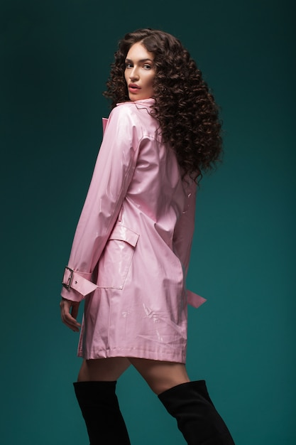 Portrait of a brunette girl with curly hair in sunglasses and a pink lacquer coat Premium Photo